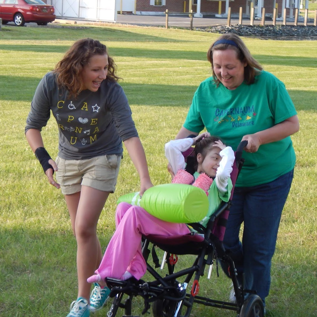 Two Embrace volunteers pushing a child in a wheelchair